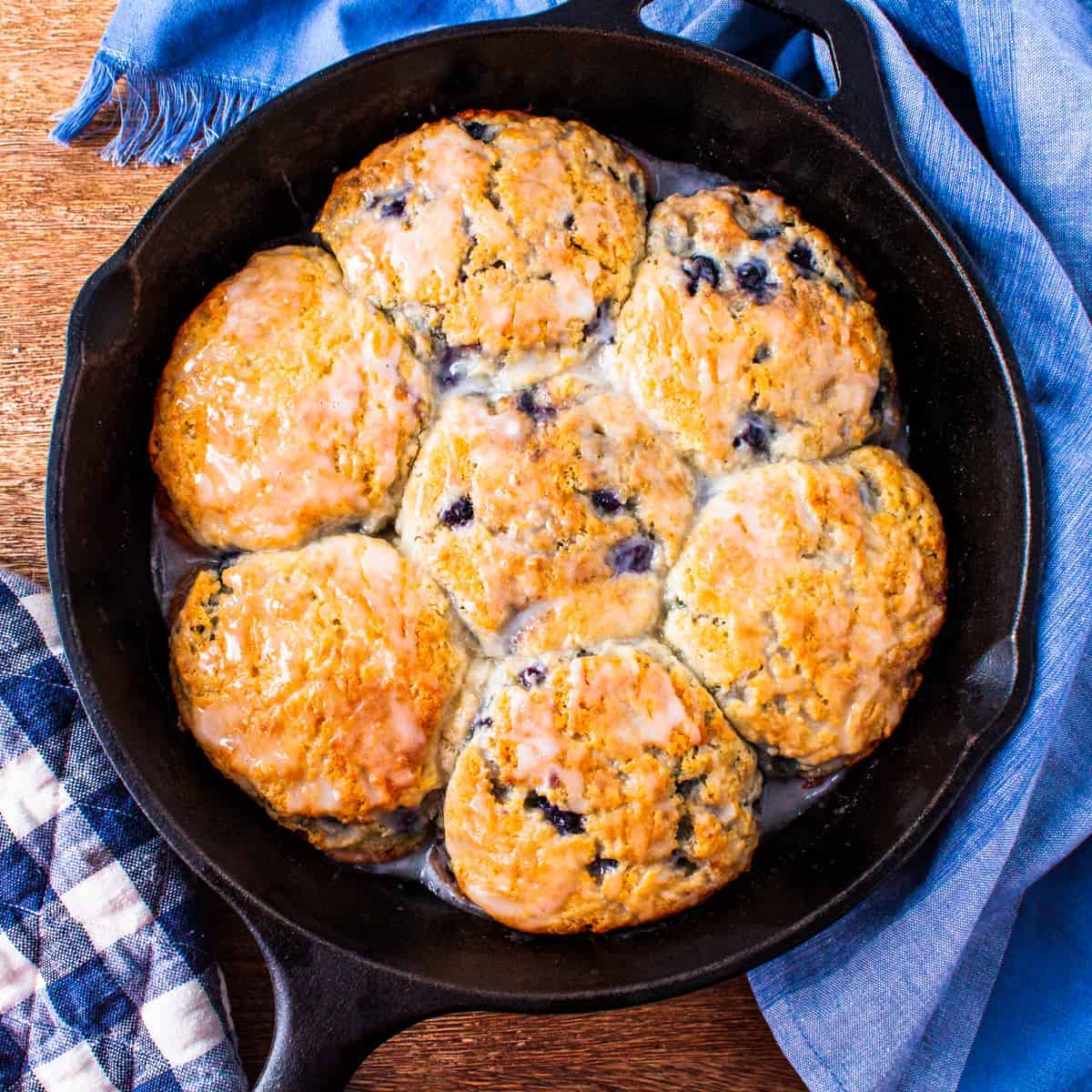 Overhead view of a cast iron skillet full of golden brown glazed blueberry biscuits.