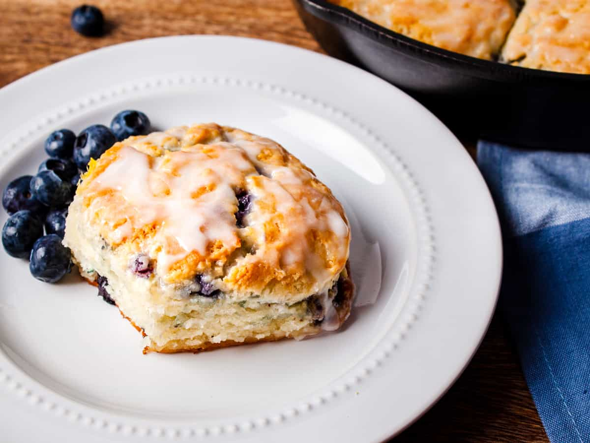 Close up view of a glazed blueberry buttermilk biscuit served on a white dish with fresh blueberries.