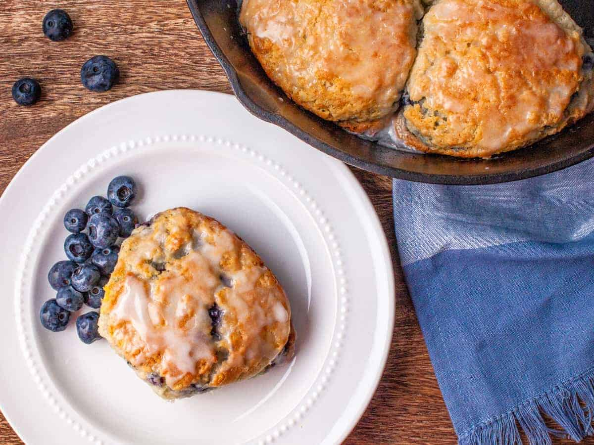 Overhead view of a biscuit served on a white dish next to a cast iron skillet of blueberry buttermilk biscuits.