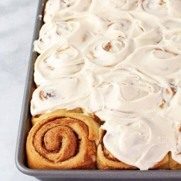 overhead view of a pan of fresh baked cinnamon rolls covered with icing.