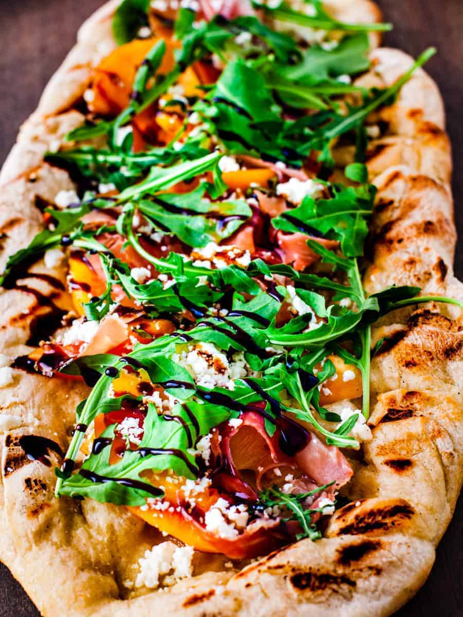 Close up image of grilled pizza topped with fresh peaches, arugula, prosciutto, and goat cheese then drizzled with balsamic glaze.
