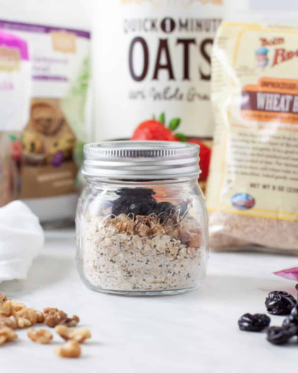 Small jar of homemade instant oatmeal shown surrounded by packages of oatmeal, wheat bran, chia seeds, and ground flax seeds.