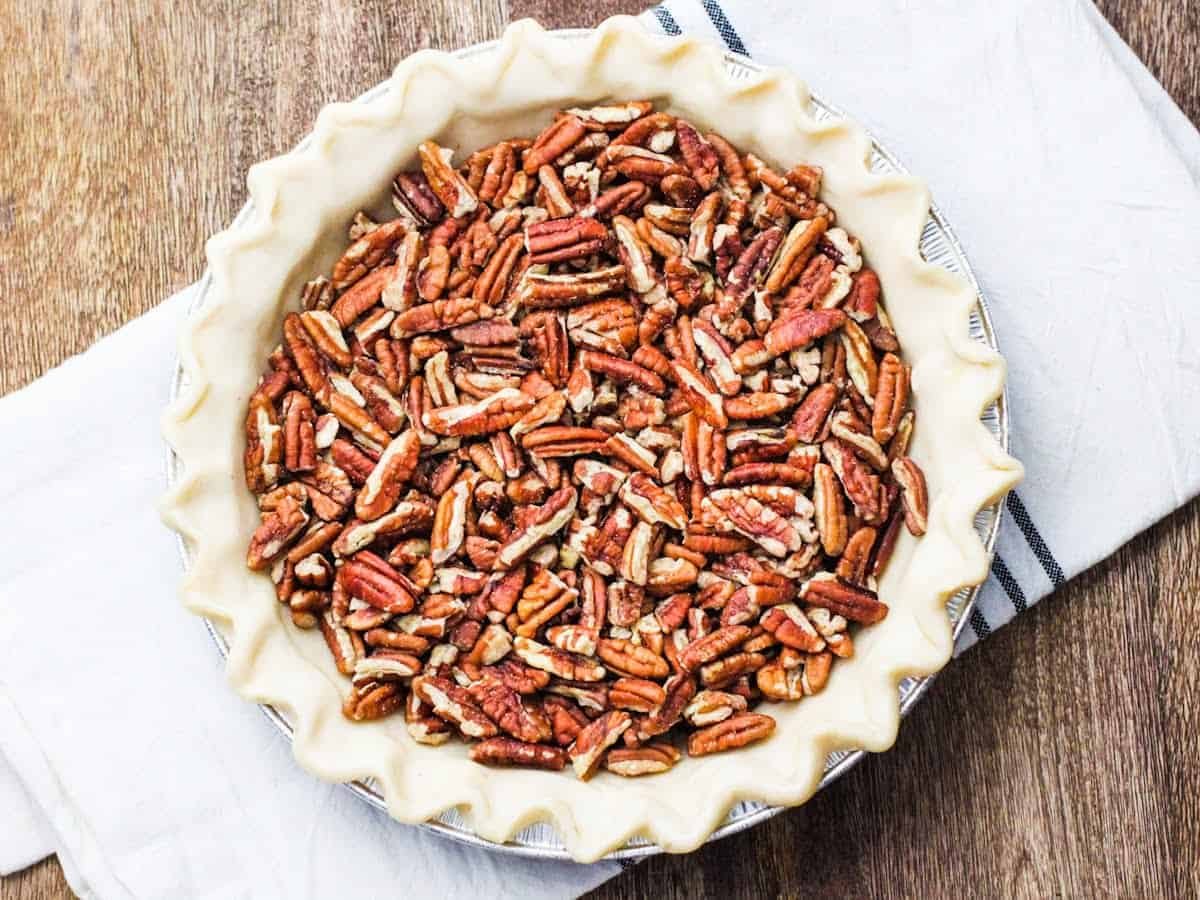 Overhead view of an unbaked pie crust filled with chopped pecans.