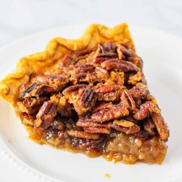 Side angle view of a large slice of pecan pie served on a white dish.