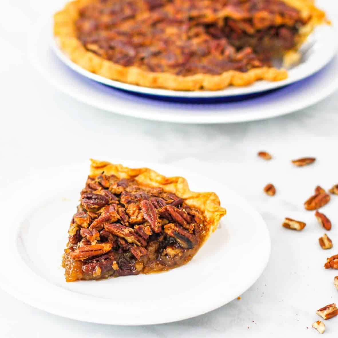 Side angle view of a large slice of pecan pie set next to the whole pie dish.