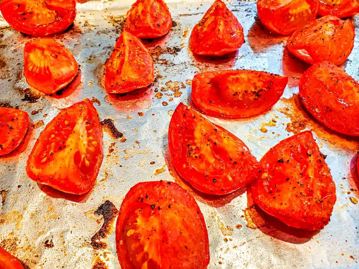 Close up view of oven roasted tomatoes on a baking sheet.
