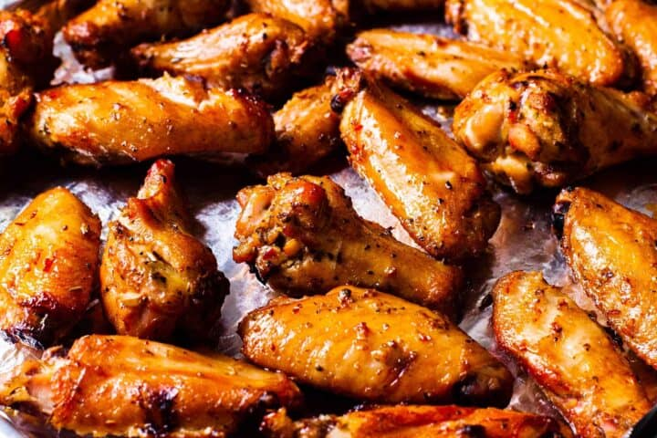 Side view of a rimmed baking sheets filled with golden brown smoked chicken wings.