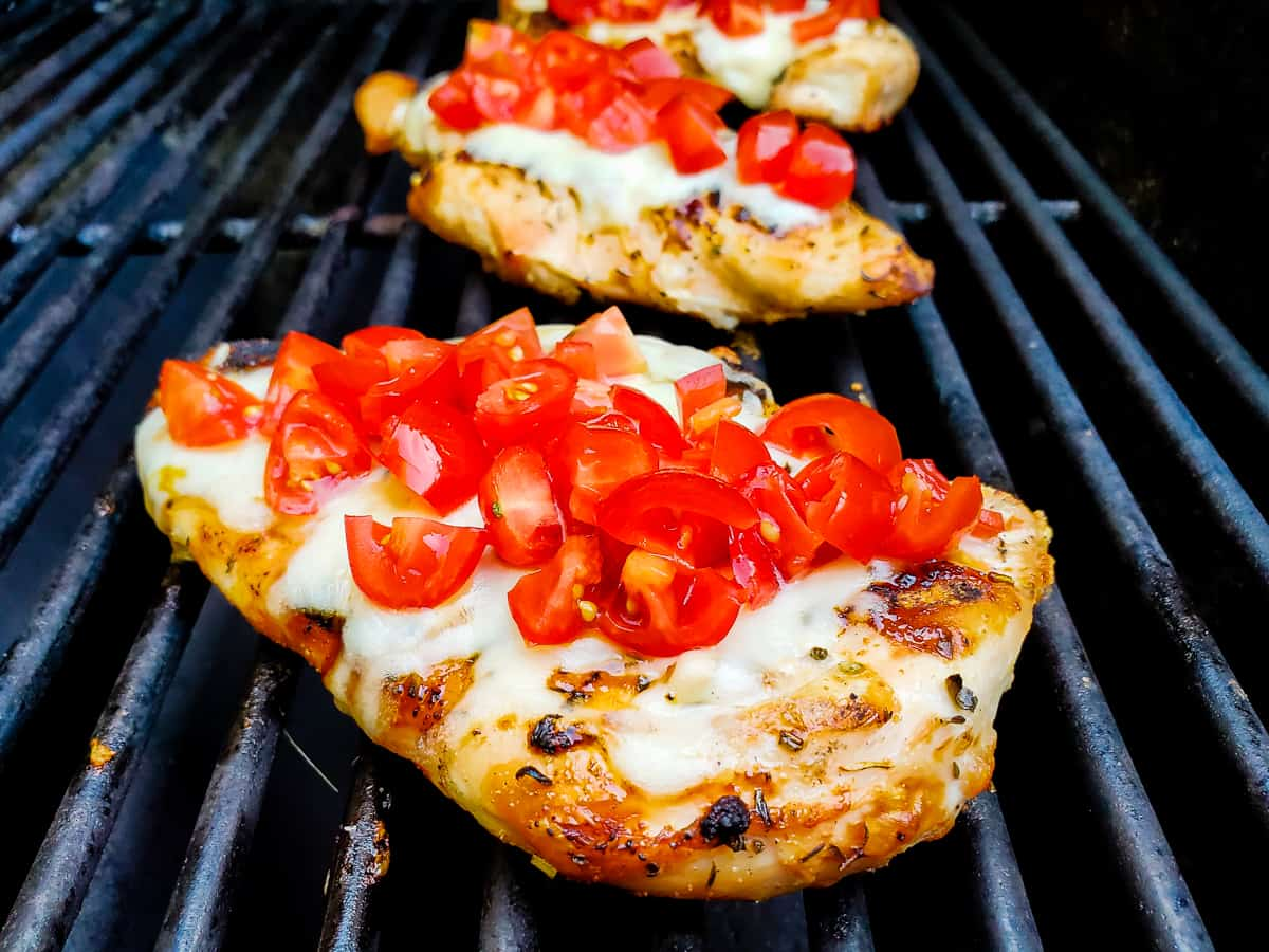 Chicken breast shown on a grill topped with cheese and chopped tomatoes.