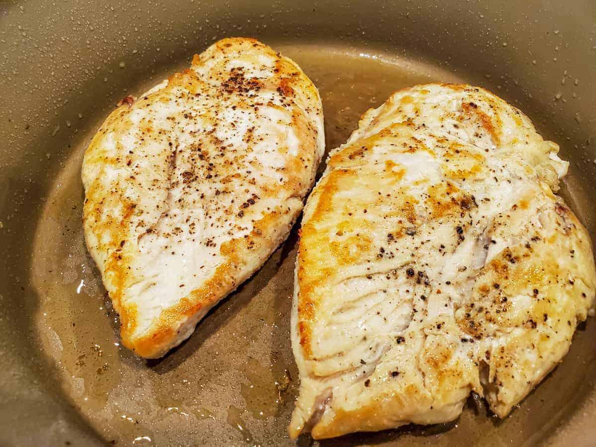 Chicken being sautéed in a pan.