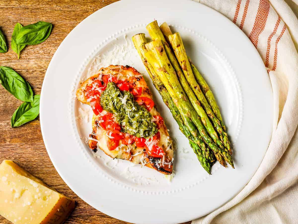 Overhead image of a plate of grilled chicken caprese served with grilled asparagus.