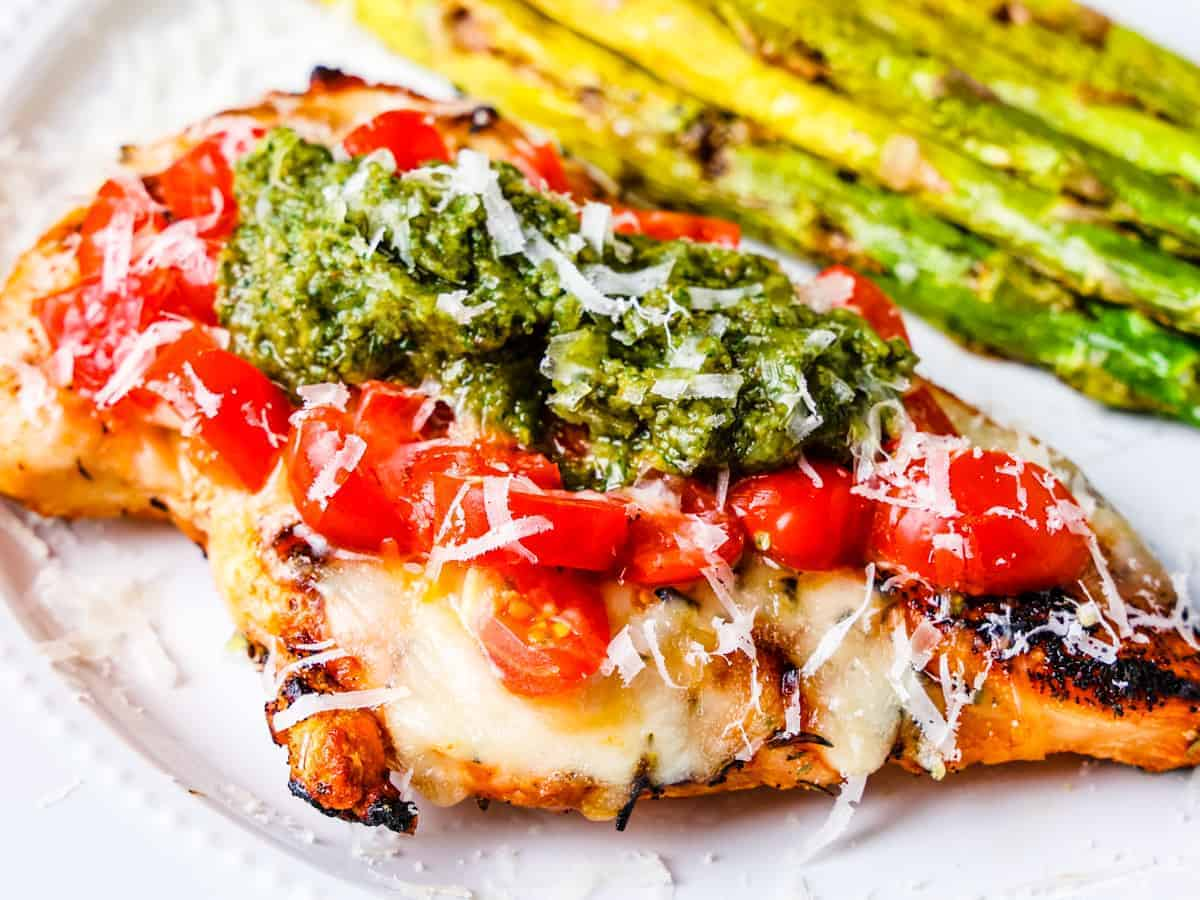 Close up view of a serving of grilled chicken caprese with pesto.