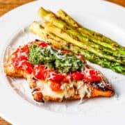 Side angle view of a grilled chicken breast topped with mozzarella cheese, chopped cherry tomatoes, and basil pesto served with a side of grilled asparagus.
