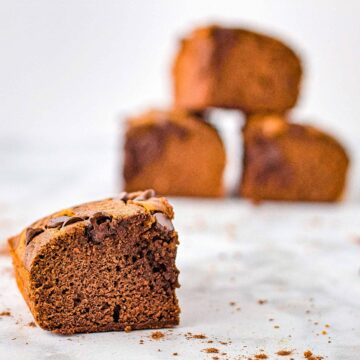 A single chocolate pumpkin swirl brownie is set on a counter with a stack of brownies blurred in the background.