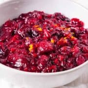 Homemade cranberry sauce served in a white bowl and topped with orange zest.