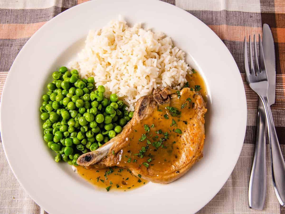 Overhead image of the finished pork chops served with rice and peas.