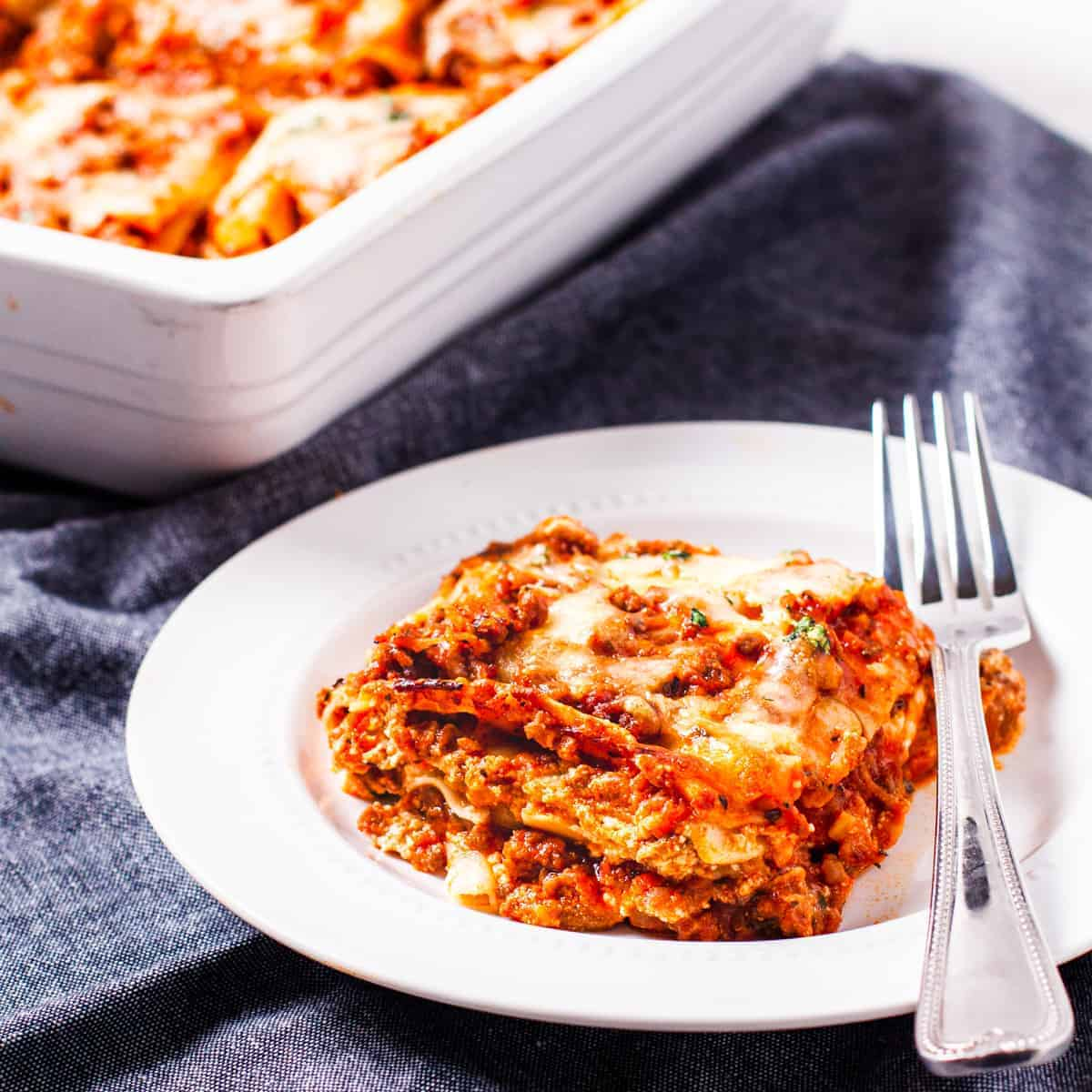 Side angle view showing a serving of lasagna alongside the lasagna dish.