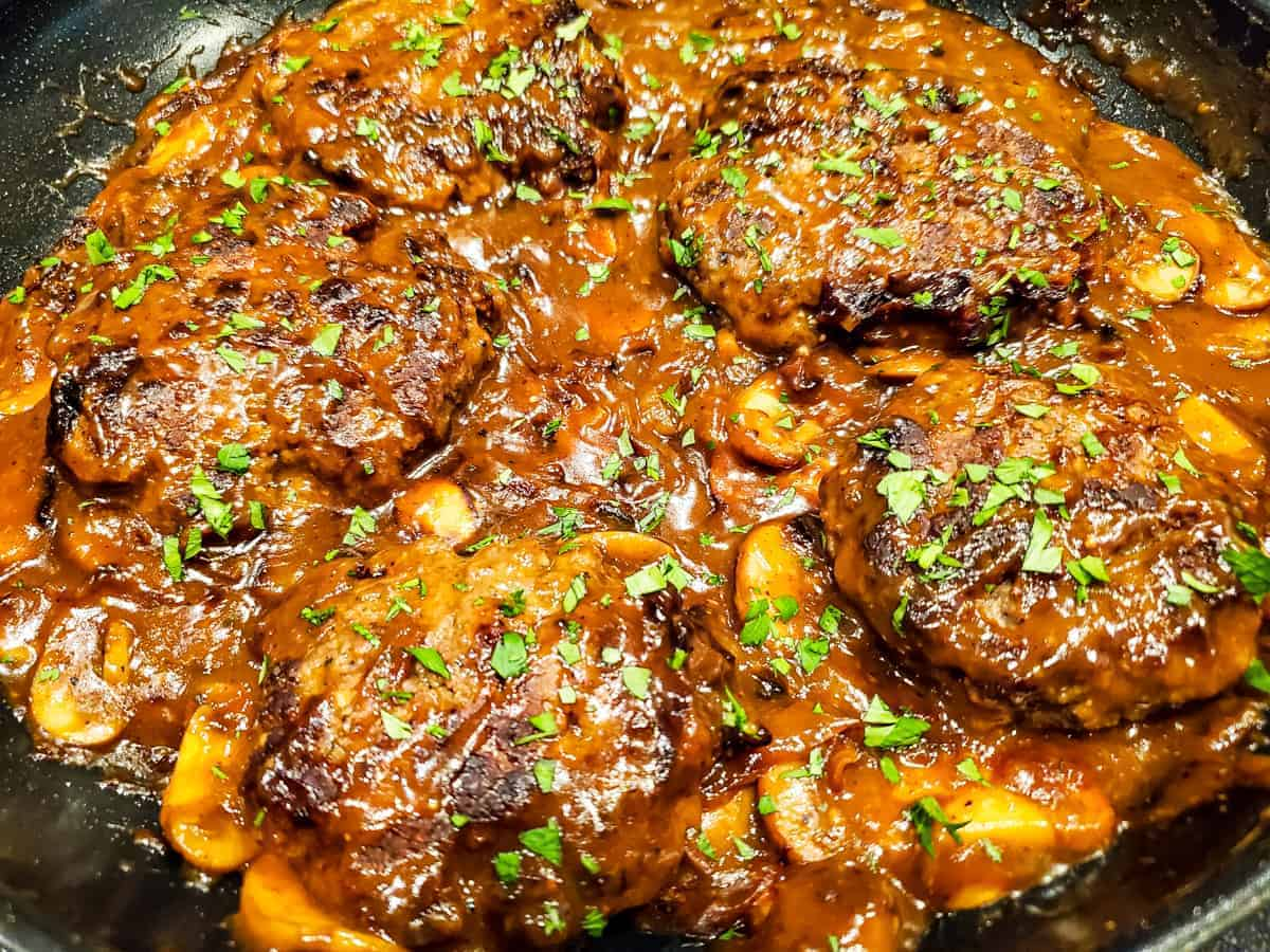 Image of the finished hamburger steaks shown in the pan with the mushroom gravy ready to serve.