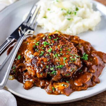 Side angle view of salisbury steak set atop a mushroom gravy and served with a side of creamy mashed potatoes.