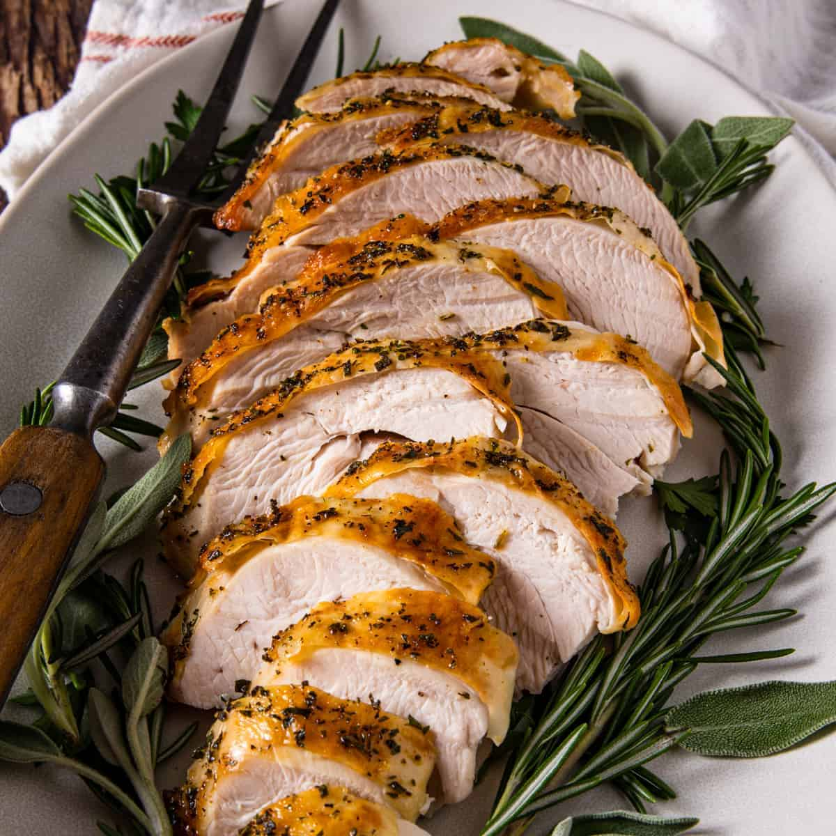 Close up view of the sliced herb roasted turkey on a serving platter surrounded by fresh herbs for garnish.