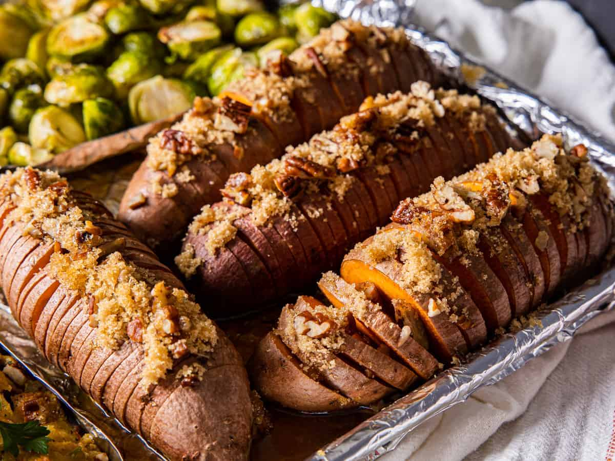 Close up view of the hasselback sweet potatoes topped with brown sugar and pecans.