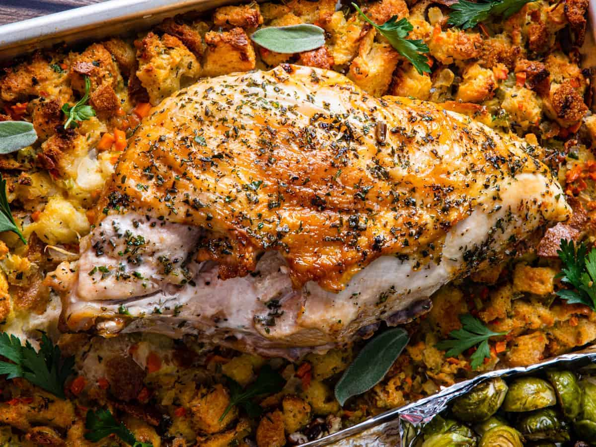 A close up shot of the herb roasted turkey breast set on top of the stuffing.