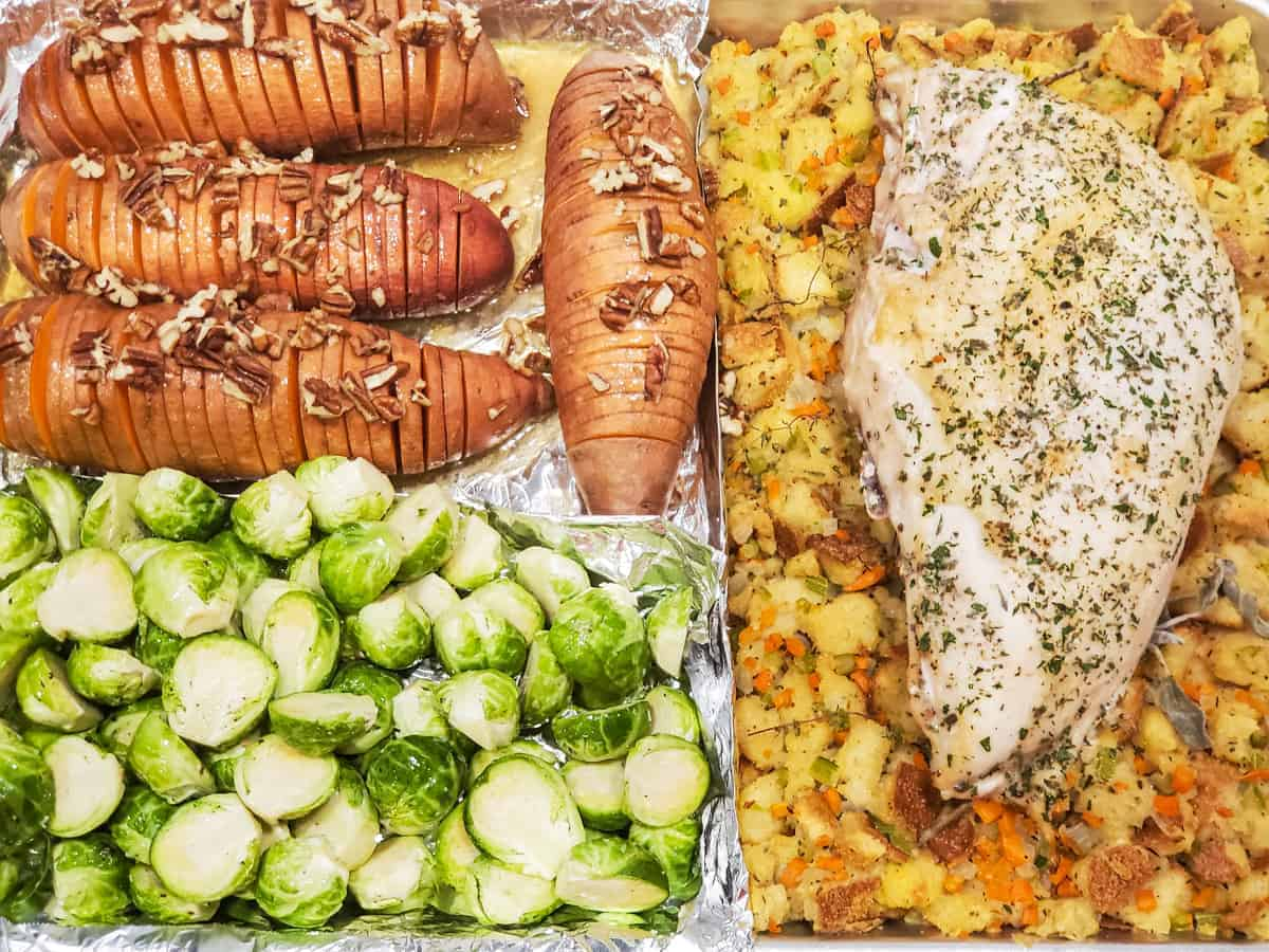 The sheet pan is shown with the brussels sprouts added to the pan alongside the sweet potatoes, turkey , and stuffing.