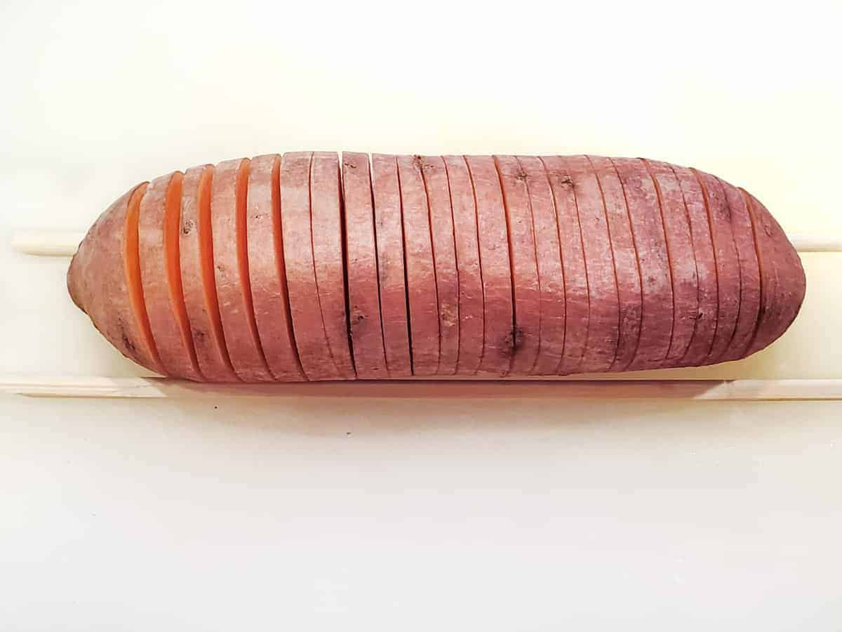 The sweet potato is then cut into thin slices about an eight to a quarter inch thick crosswise, starting around 1 inch from the end and ending 1 inch from the opposite end. The chopsticks help to keep the knife from cutting all the way through the sweet potato so that it remains attached..