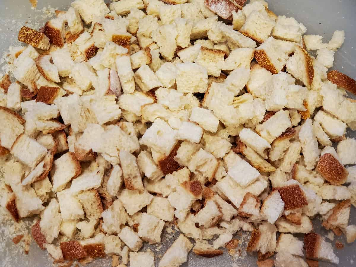 Homemade bread cubes shown on a cutting board.
