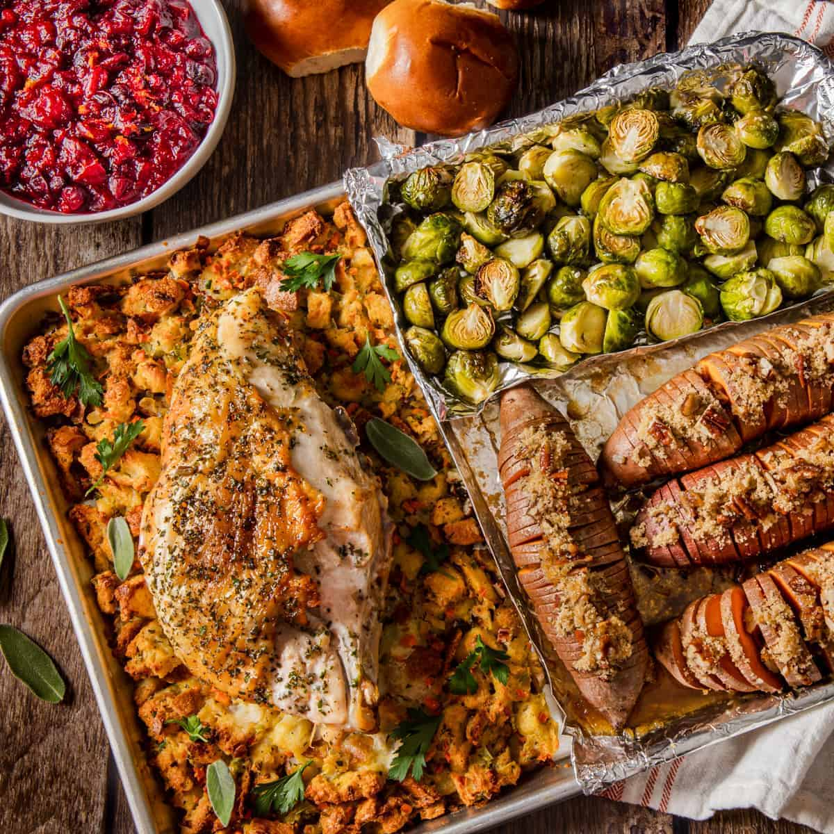 Overhead view of a table set with a sheet pan of roasted turey and stuffing with vegetables accompanied by a bowl of cranberry sauce and rolls.