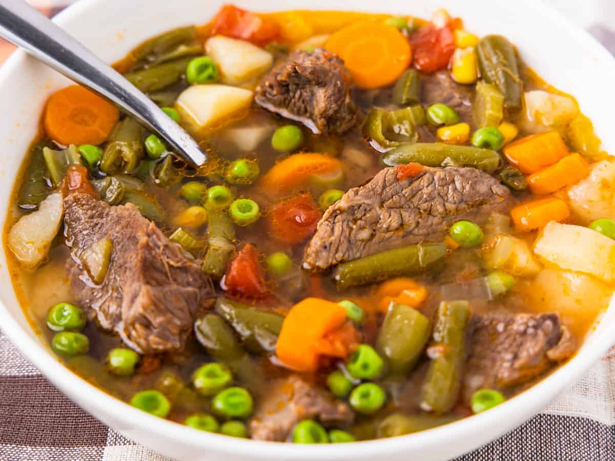 Close up view of the finished soup showing chunks of beef with vegetables in a beef broth.