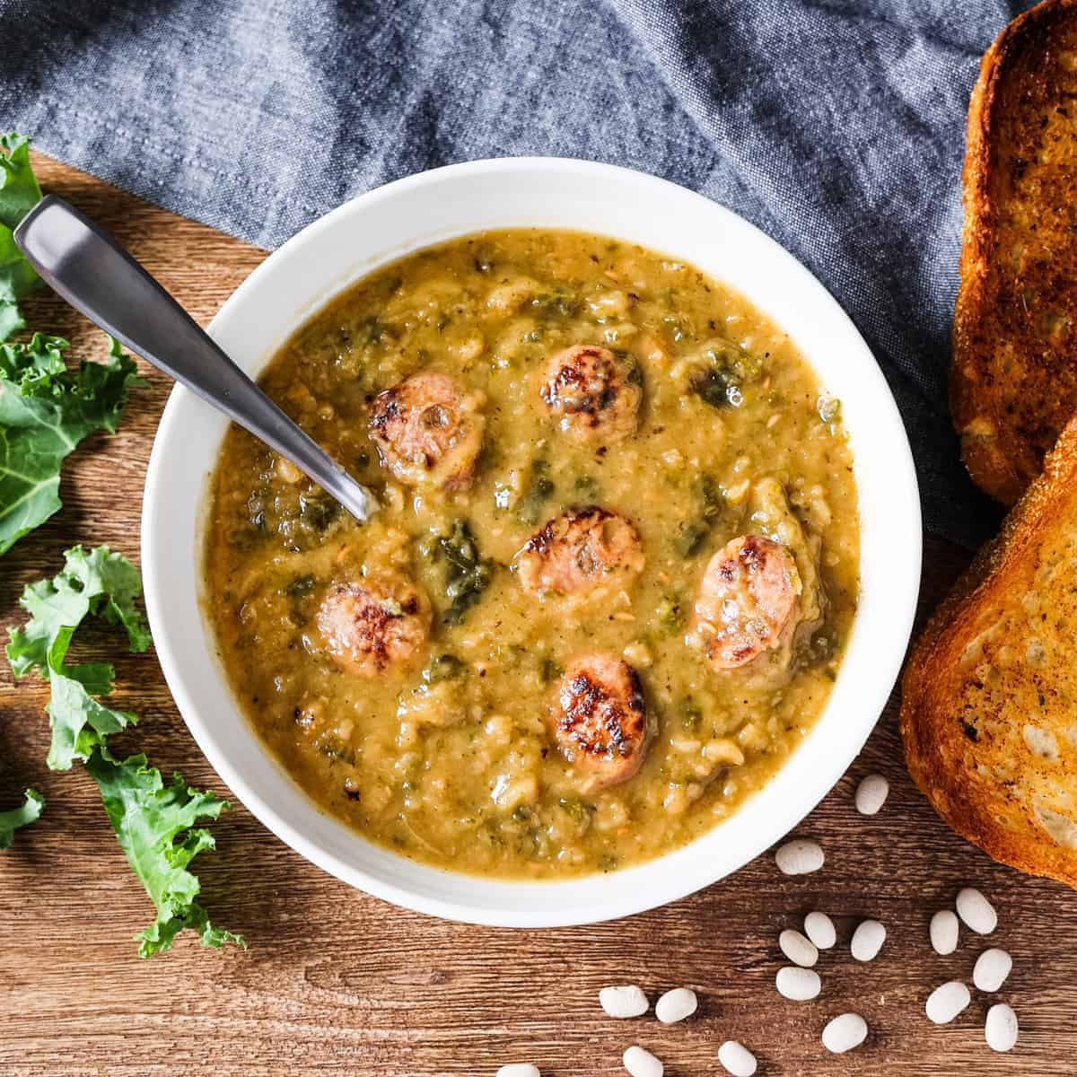 Overhead view showing a bowl of white bean soup with kale and chicken sausage served with a side  of garlic bread.