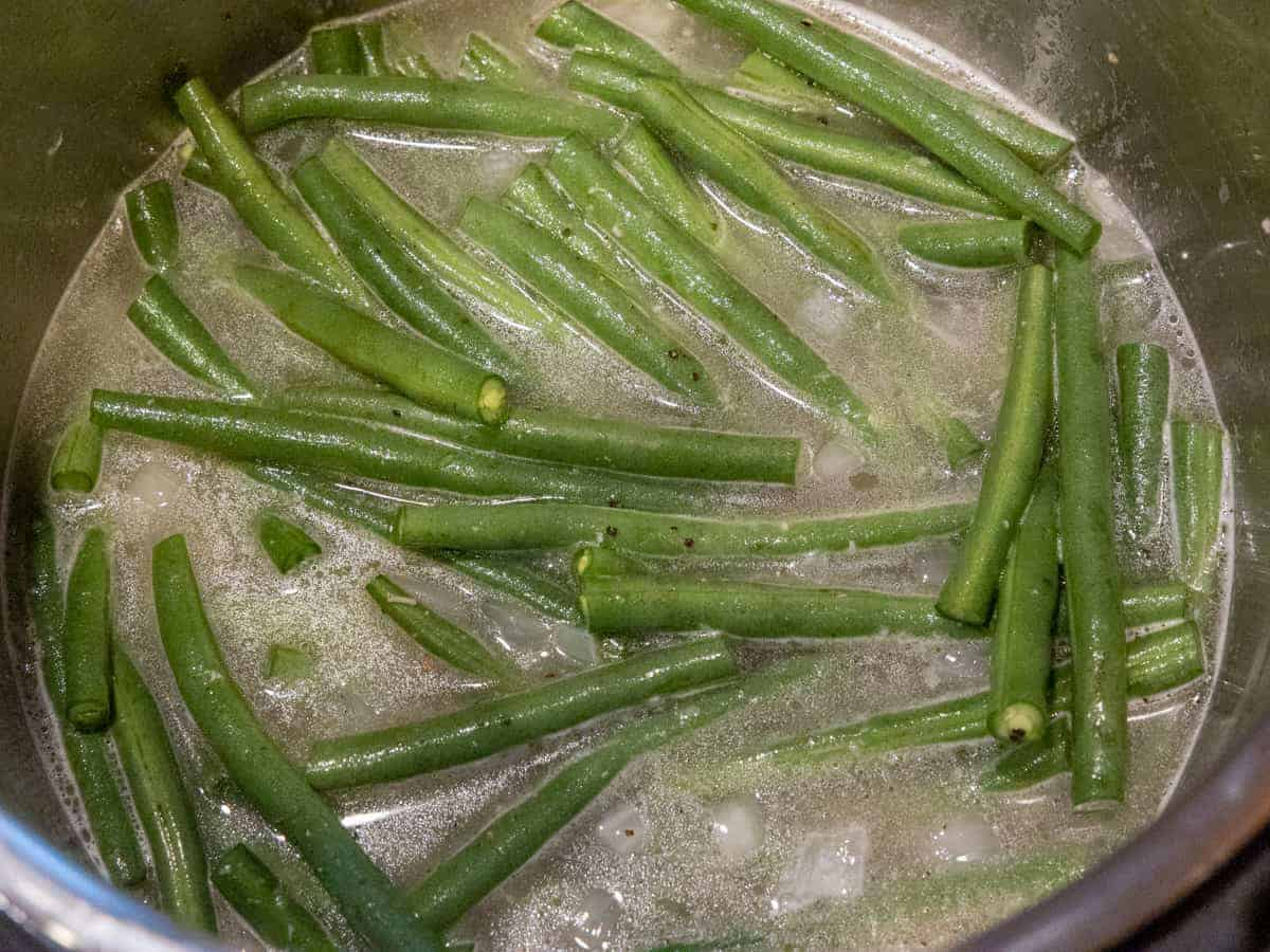 Process shot showing the green beans in the broth and onion mixture before pressure cooking.