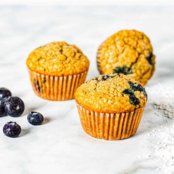 Three blueberry muffins shown on a countertop with fresh blueberries.