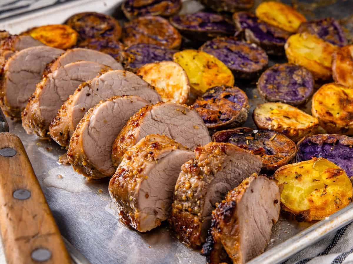 The finished pork tenderloin is shown sliced and served on the sheet pan with potatoes.