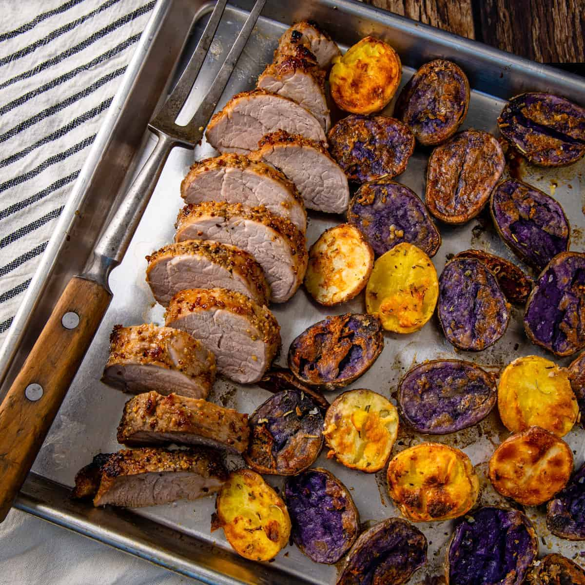 Overhead image of a sheet pan with sliced pork tenderloin and roasted parmesan potatoes.