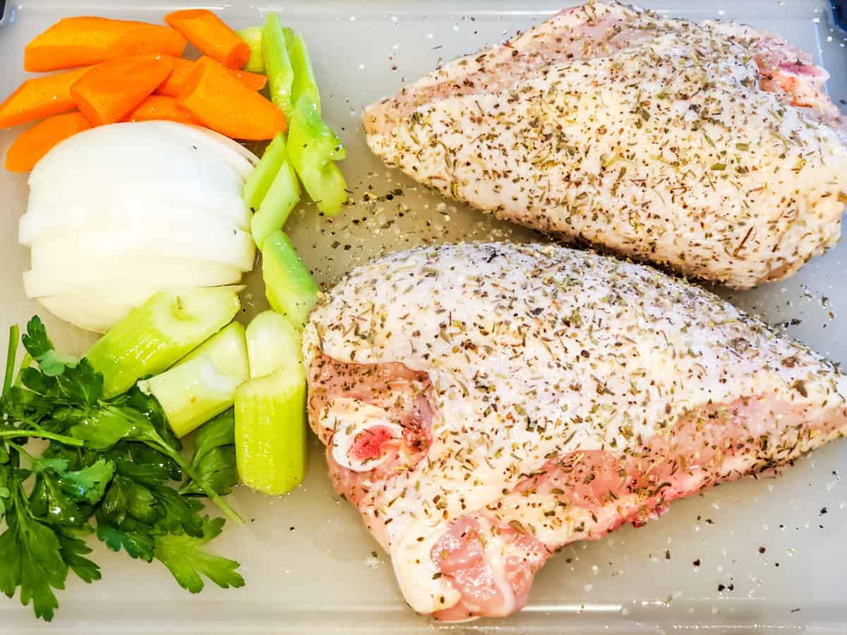 Seasoned chicken breasts and chopped vegetables shown set on a cutting board before cooking.