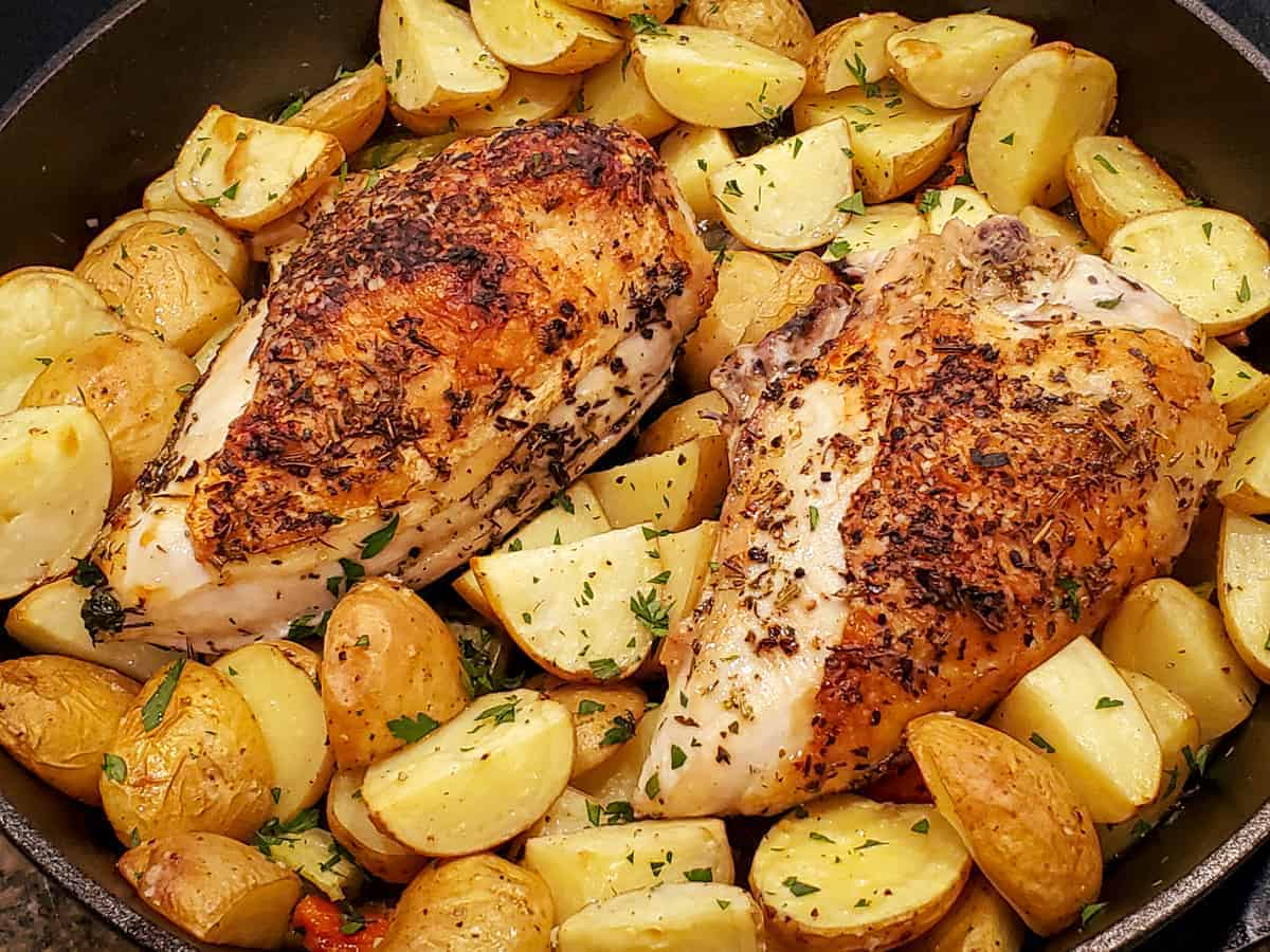 Roasted chicken breasts with crispy browned skin and roasted potatoes shown in a cast iron skillet after cooking.