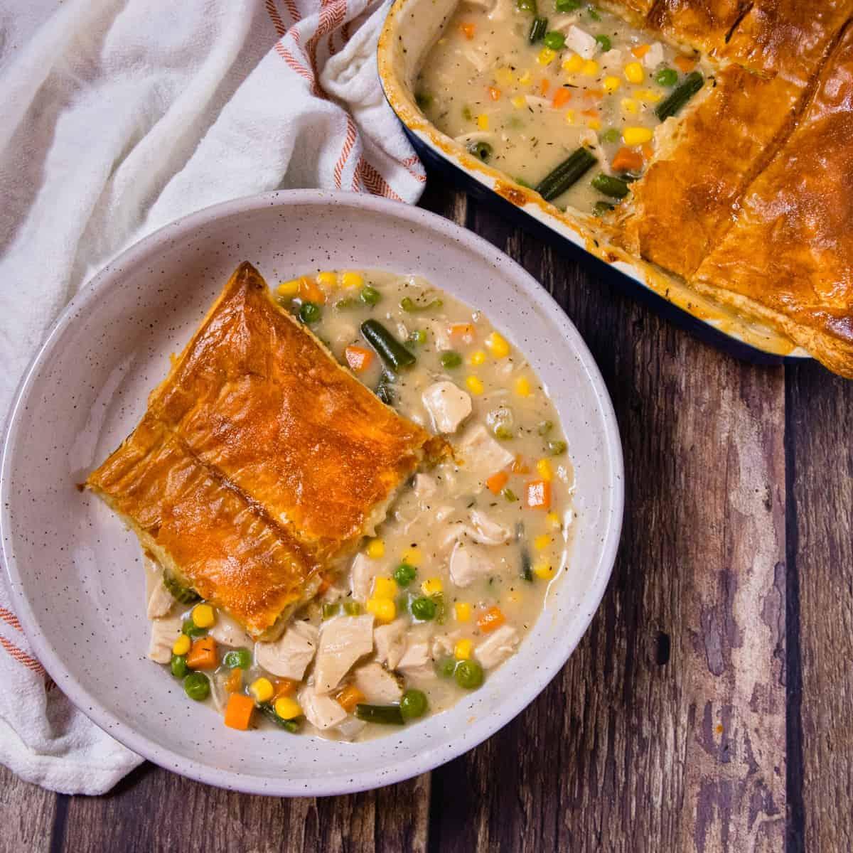 Overhead view of a plate of turkey pot pie set beside a baking dish of pot pie.