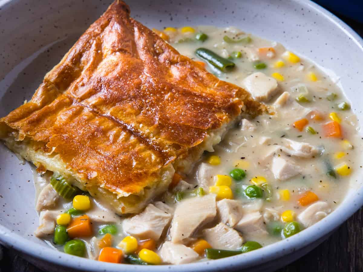 Close up view of a serving of turkey pot pie topped with a golden brown puff pastry topping.