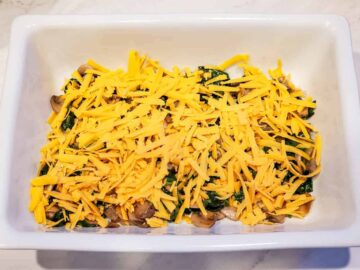 The cooked vegetable mixture is shown in the baking dish topped with shredded cheese.