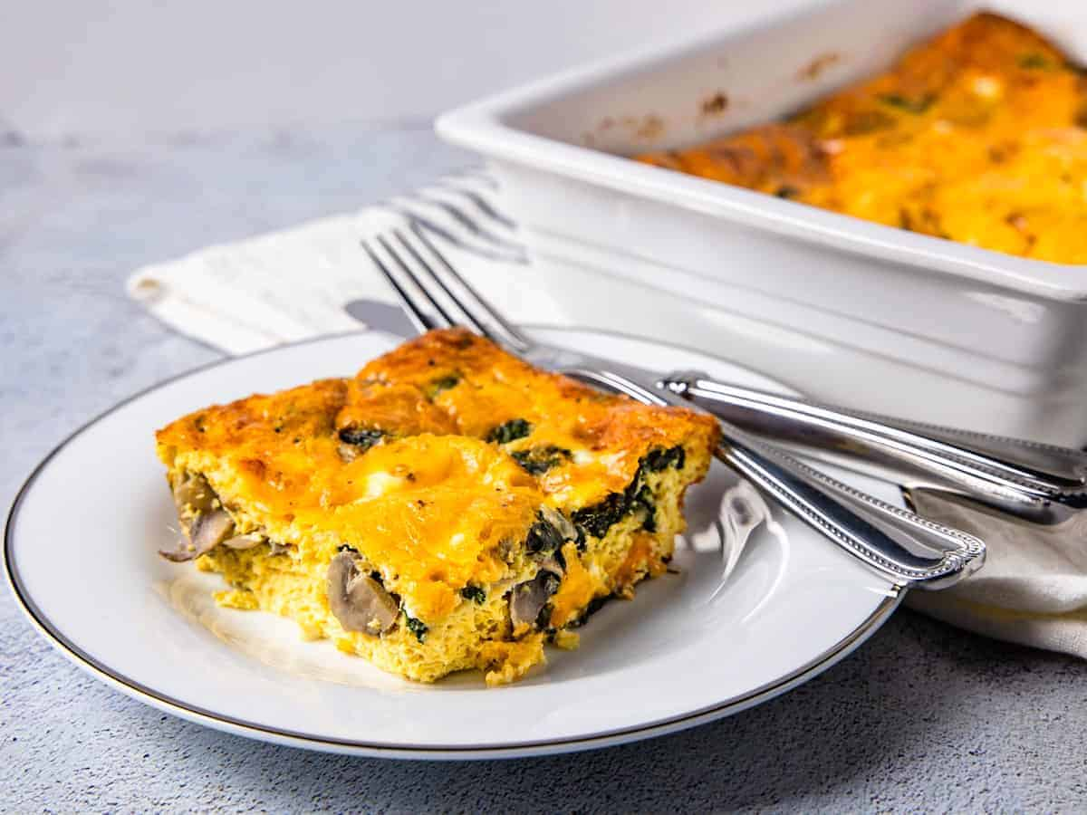 The finished breakfast casserole is shown served on a plate, set beside the casserole dish.