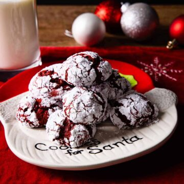Plate of red velvet crinkle cookies shown on a table with a red placemat and surrounded by Christmas ornaments.