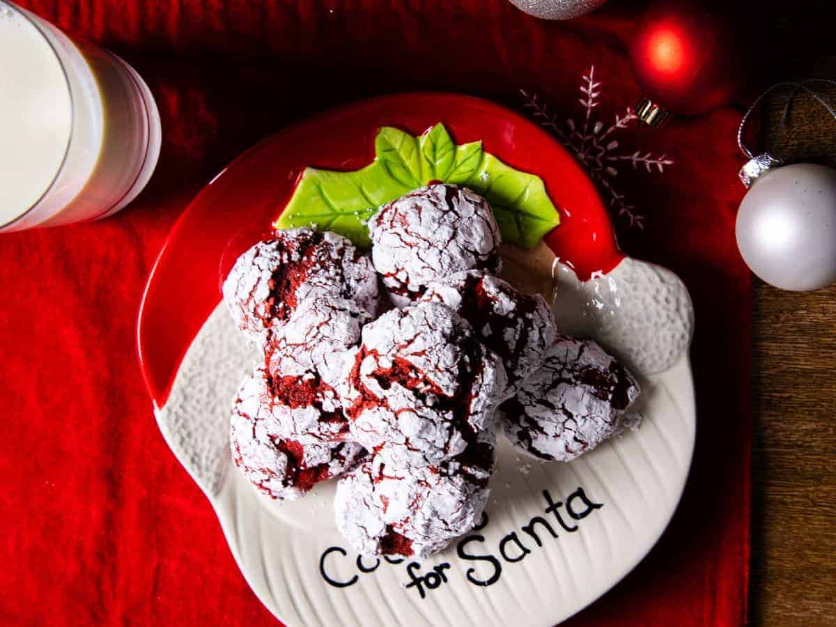Over head view of a plate of red velvet crinkle cookies set on a Christmas table.