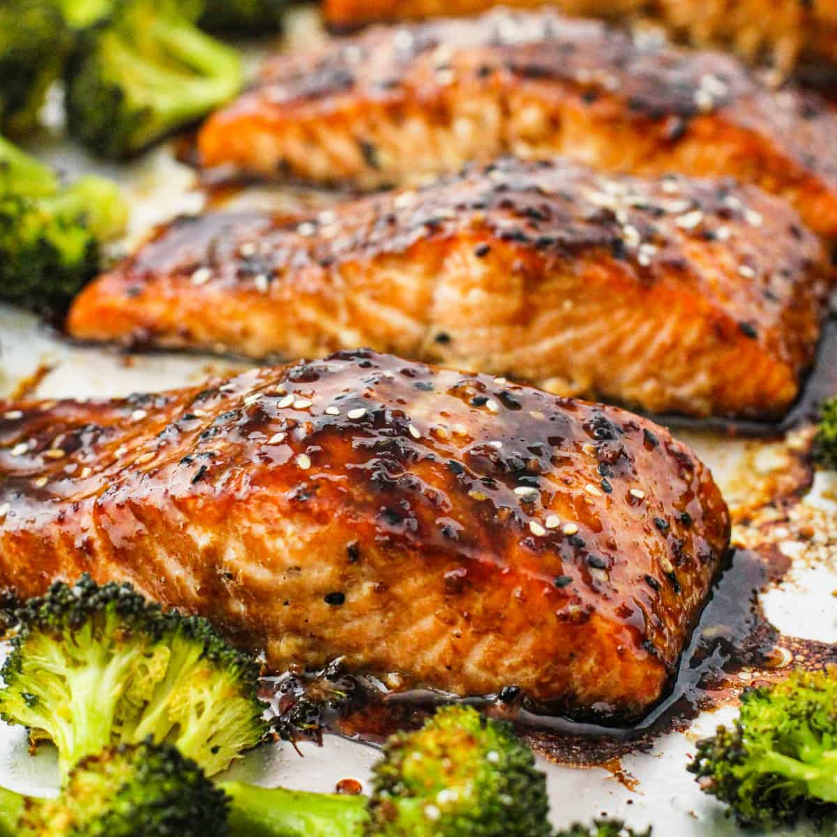 Side angle view of the completed salmon shown covered in soy ginger glaze with roasted broccoli.
