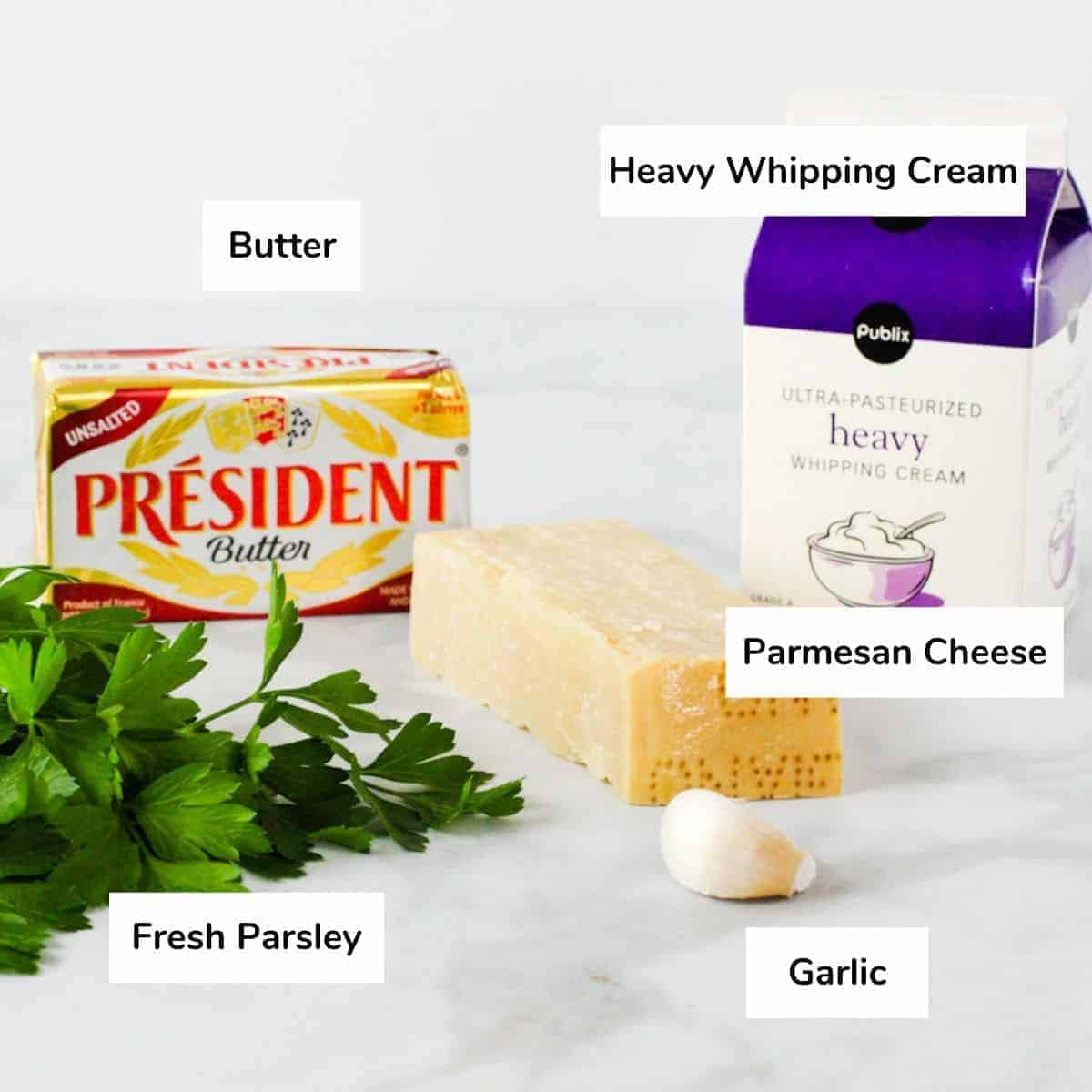 The ingredients for alfredo sauce; butter, heavy whipping cream, Parmesan cheese, garlic, and fresh parsley, are shown set on a counter.