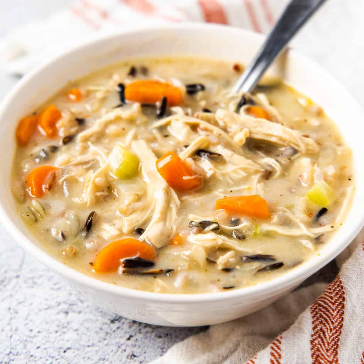 Side angle close up of a bowl of creamy chicken and wild rice soup.