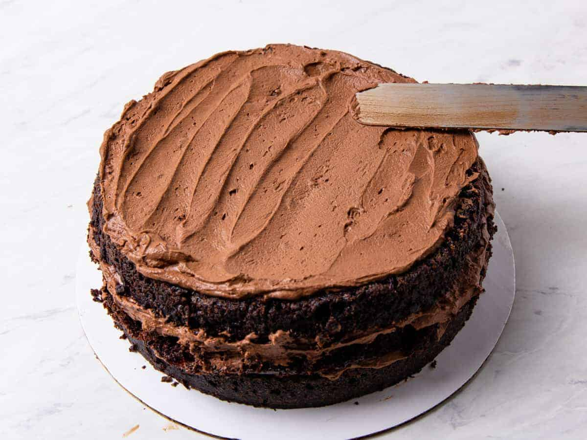 A layered chocolate cake shown being assembled with chocolate mousse being spread between layers.