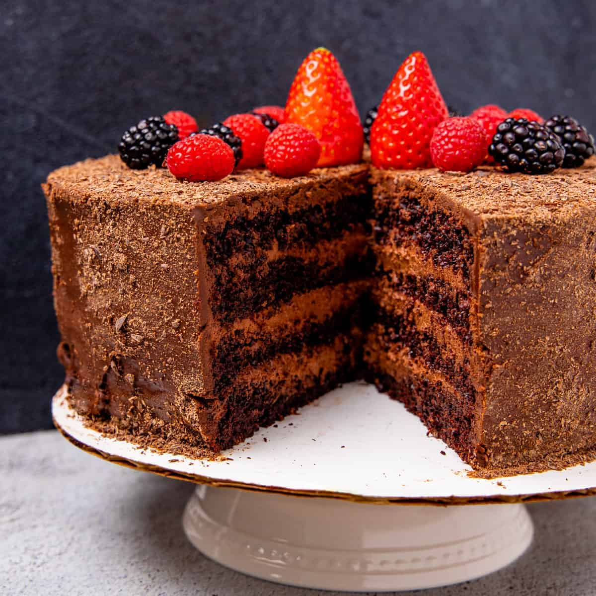A chocolate mousse cake shown layers of dark chocolate cake, chocolate mousse, and a chocolate ganache topping then garnished with fresh berries.