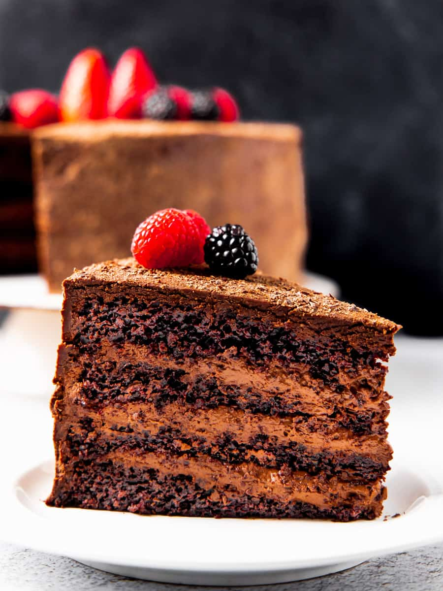 A large slice of chocolate cake layered with chocolate mousse and topped with chocolate ganache shown topped with berries.