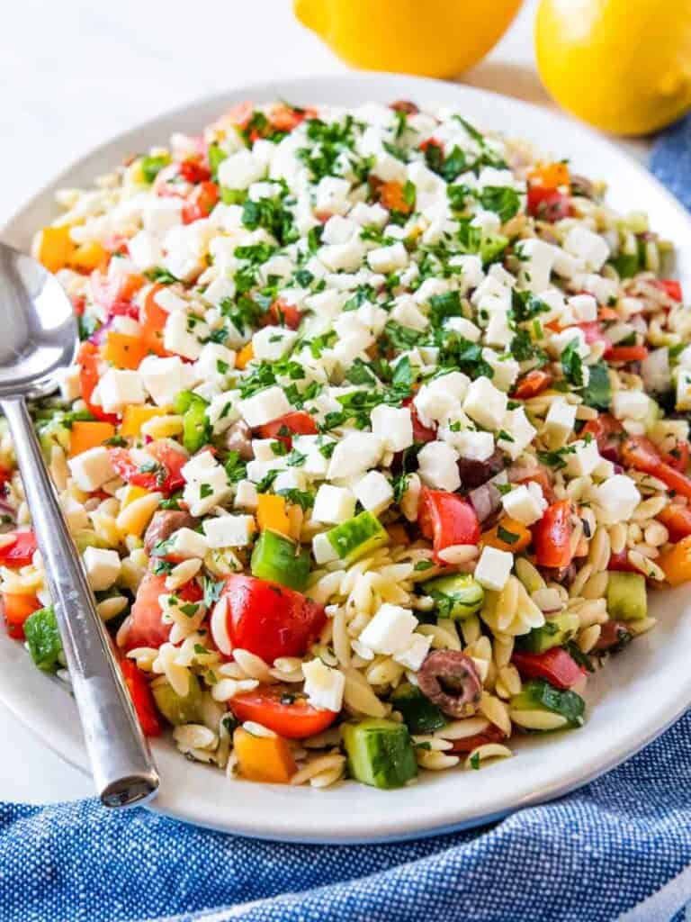 Side angle view of a serving platter piled high with Greek orzo pasta salad.